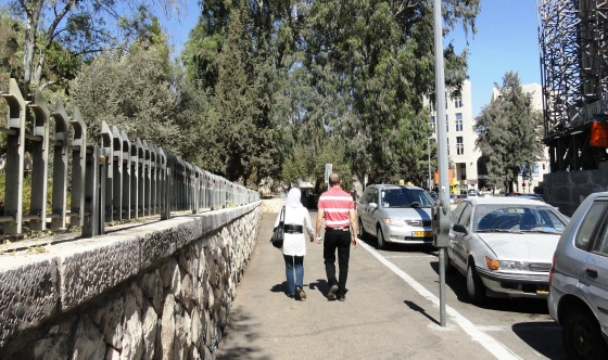 Arab man and woman holding hands in public