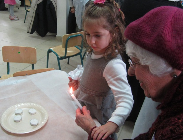 grandmother and child light candles
