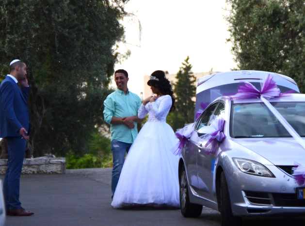 decorated car and couple taking weddnig photos