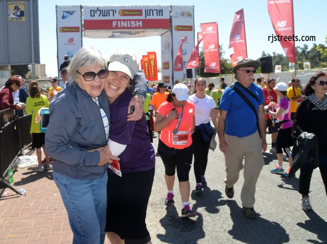 image Jerusalem marathon, photo smiling race finshers, picture grandmother hugging girl at end of race
