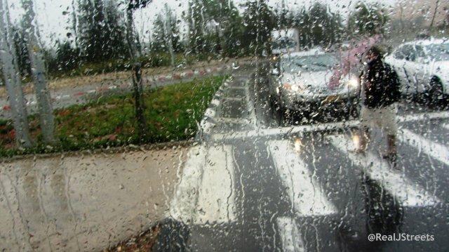 woman crossing street in rain
