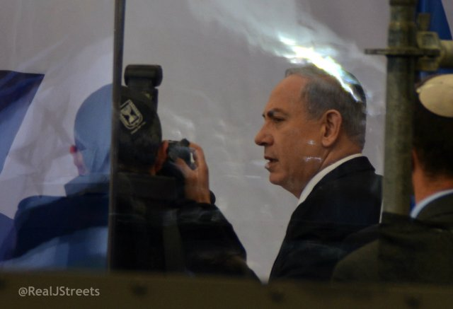 Benjamin Netanyahu speaking behind bullet proof glass