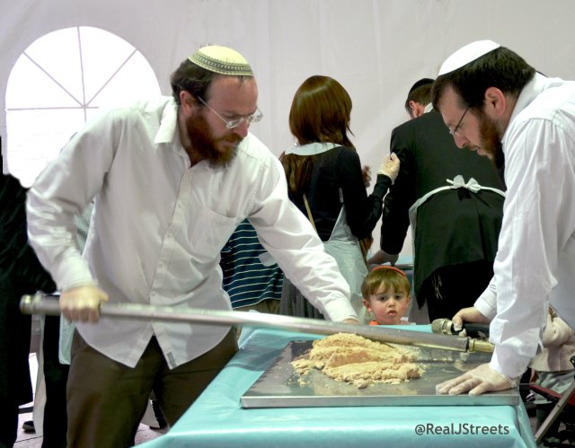 men making matza as child watches