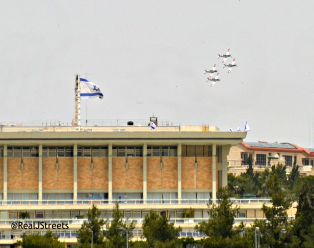 Knesset building with four planes flying near