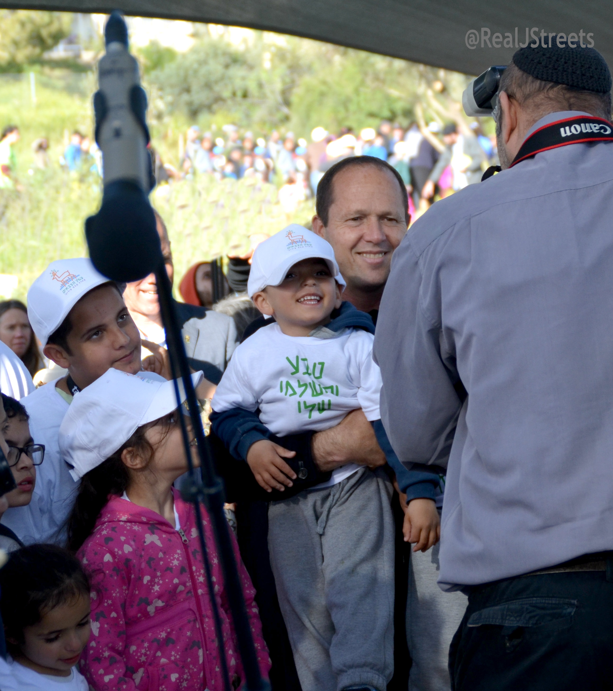 Jerusalem mayor Nir Barkat smiling with children taking photos