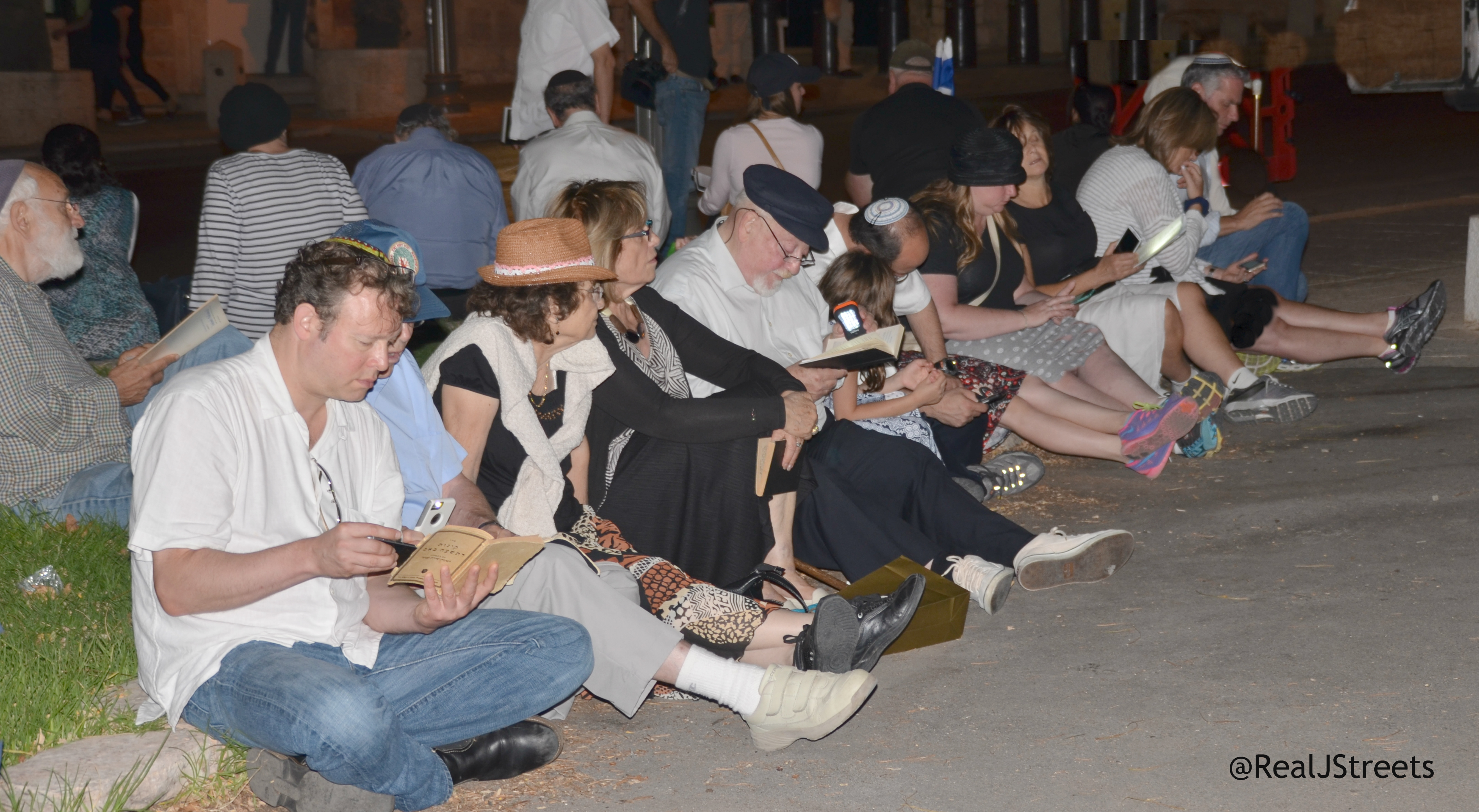 people sitting on stones for Tisha B'Av