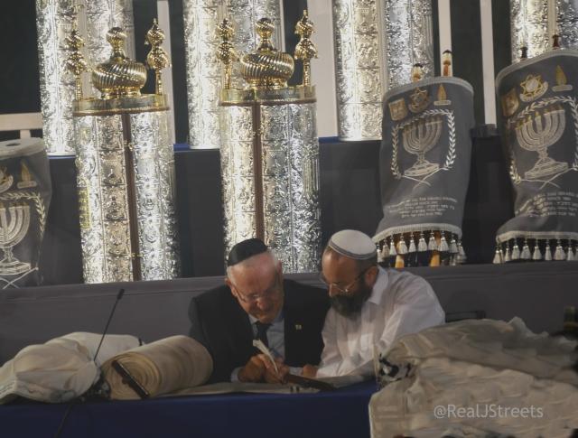 Presient Rivlin writing letter in Torah