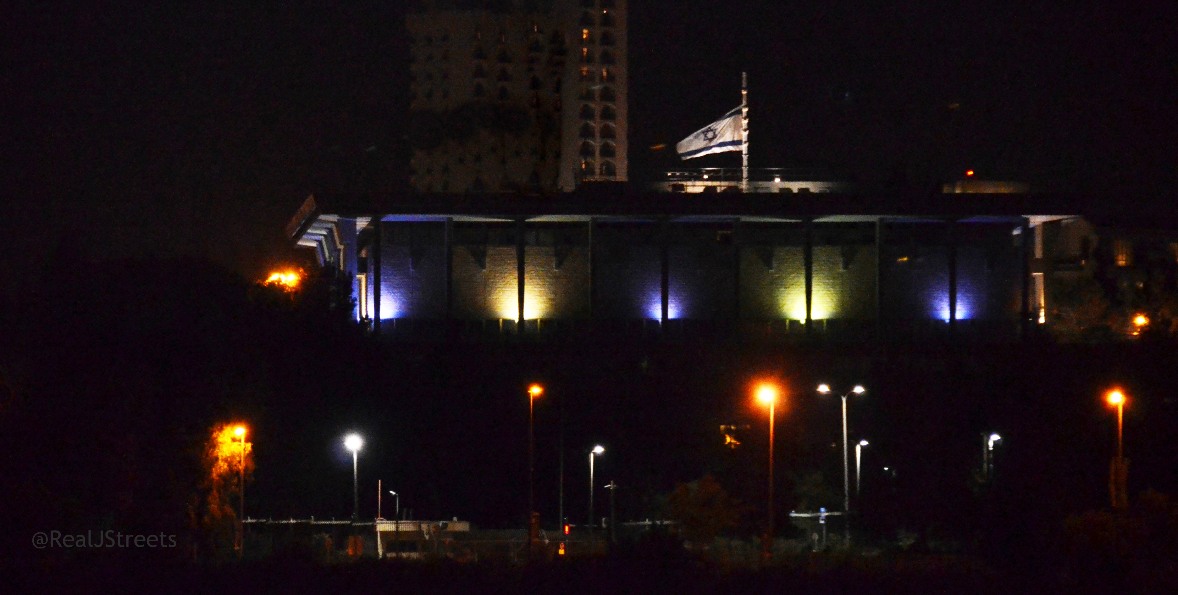 Knesset lit at night flag at half mast