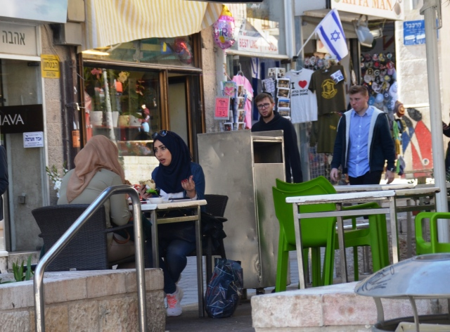 two arab girls eating in outdoor cafe
