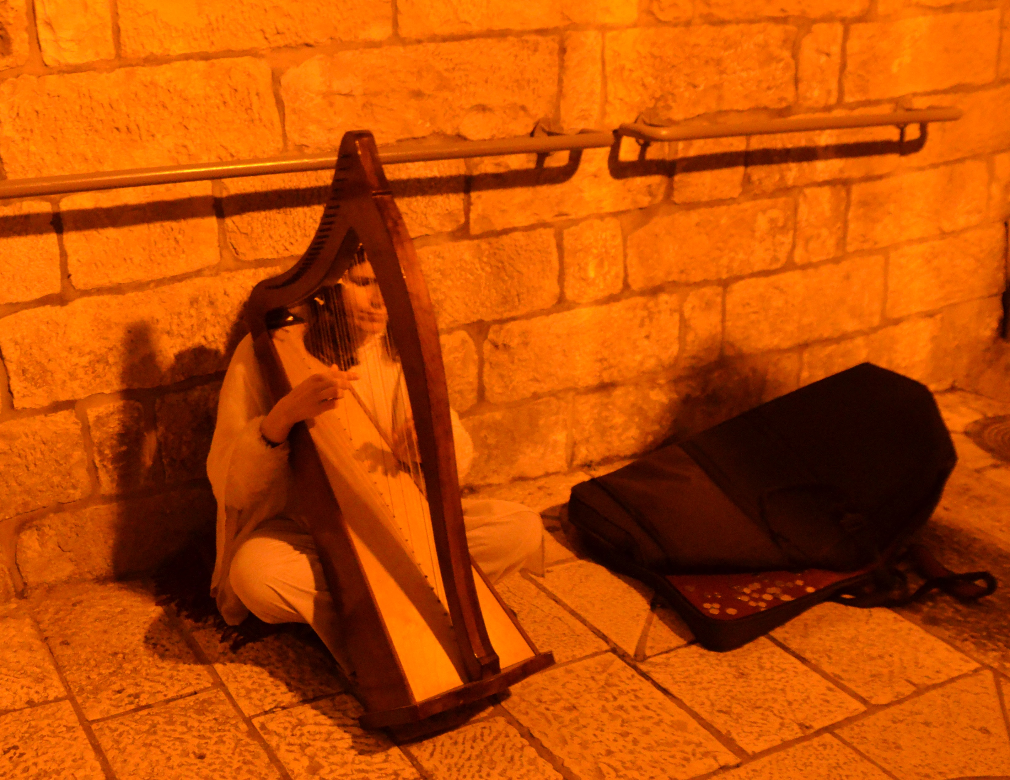 woman playing harp in Old City at night