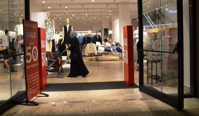 Muslim woman shopping alone at night