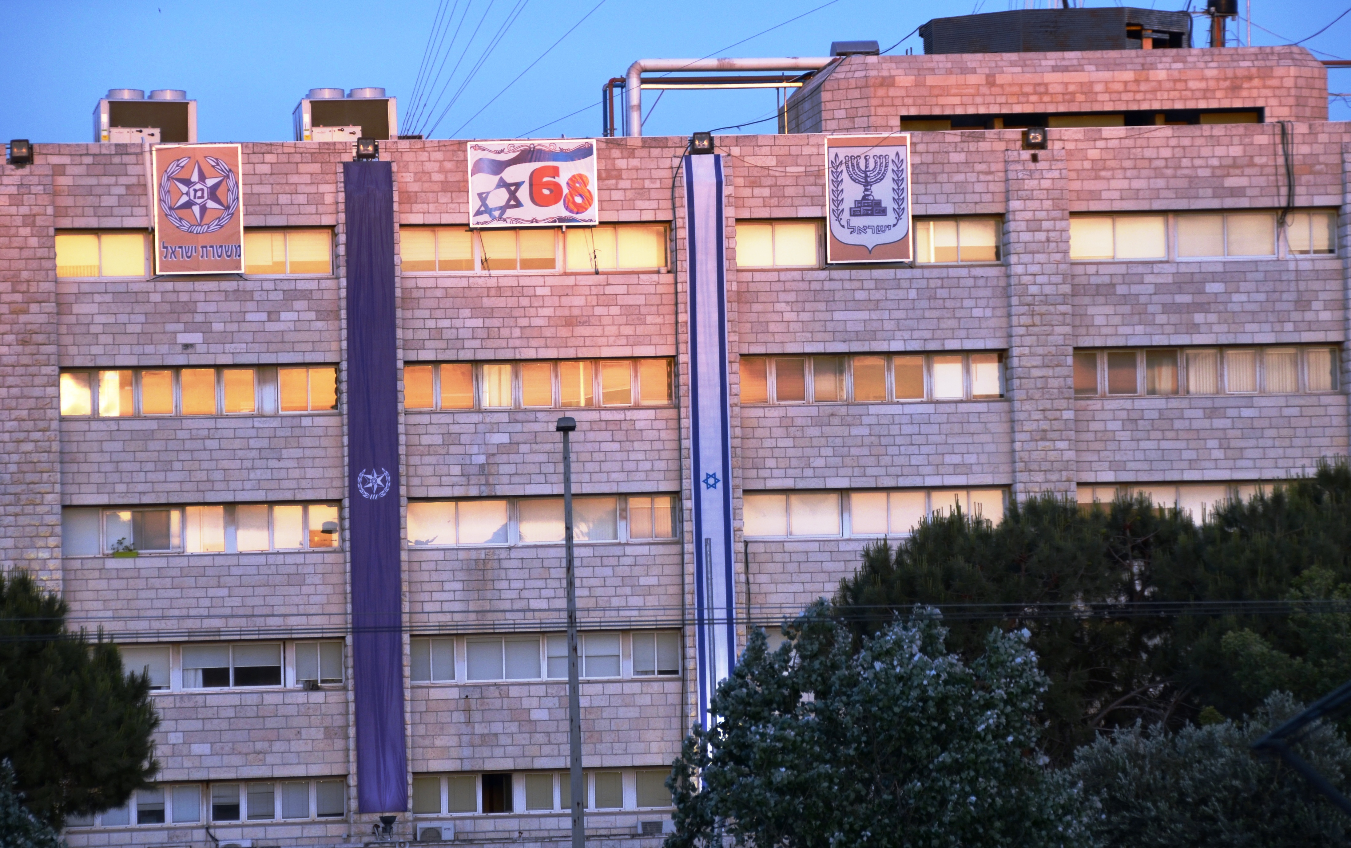 Israeli flags draped down side of police station