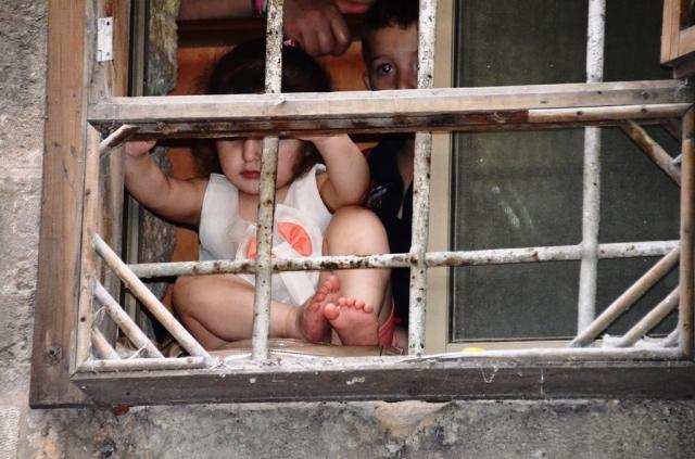Little Arab girl in window watch Flag Parade in shuk
