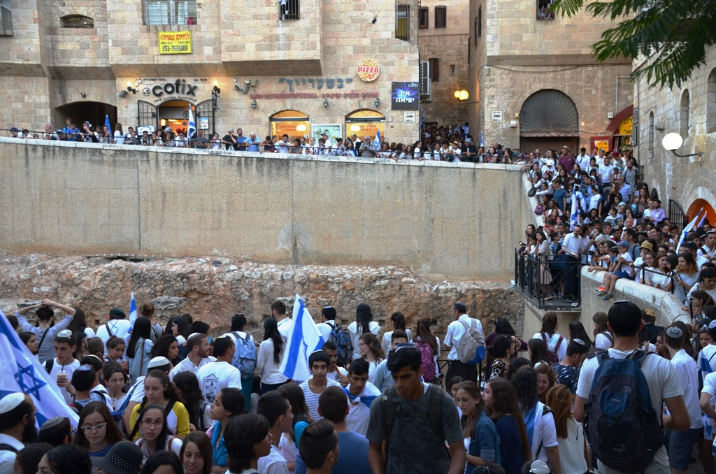 Cardo full of people on Jerusalem Day singing dancing and watching.