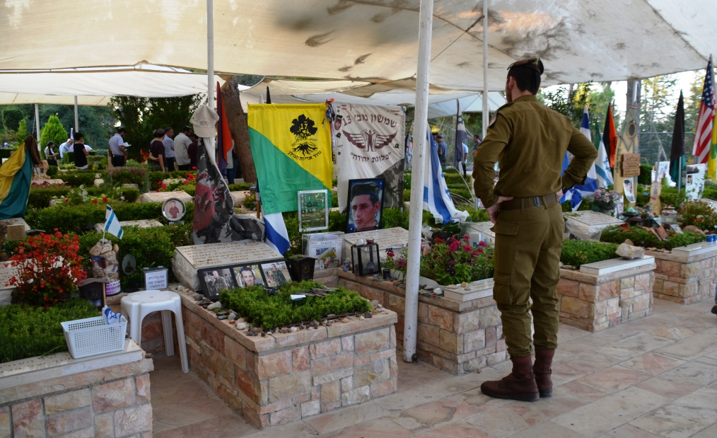 memorial service at Har Herzl soldier stands near grave stone