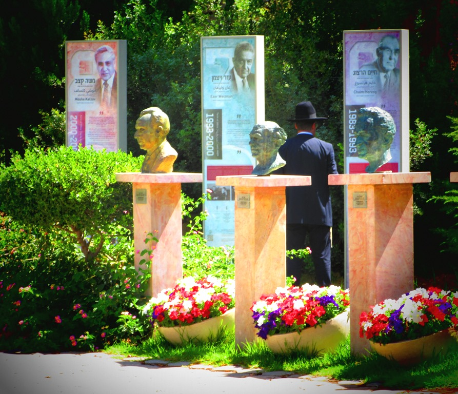Man attending dayanim ceremony reading posters of past presidents